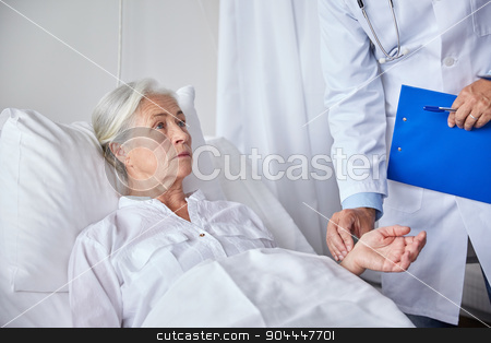 doctor checking senior woman pulse at hospital stock photo, medicine, age, health care and people concept - doctor with clipboard visiting senior patient woman and checking her pulse at hospital ward by Syda Productions
