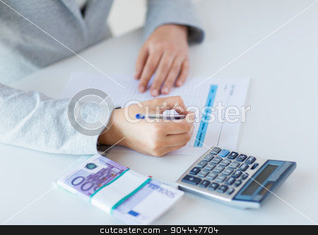 close up of hands counting money with calculator stock photo, business, finance, tax and people concept - close up of woman hands counting euro money with calculator and tax report form by Syda Productions