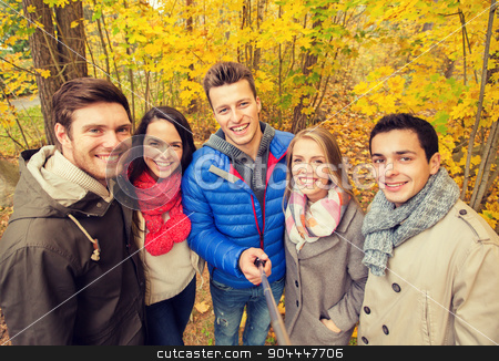 smiling friends taking selfie in autumn park stock photo, season, people, technology and friendship concept - group of smiling friends with smartphone or digital camera and selfie stick taking picture in autumn park by Syda Productions