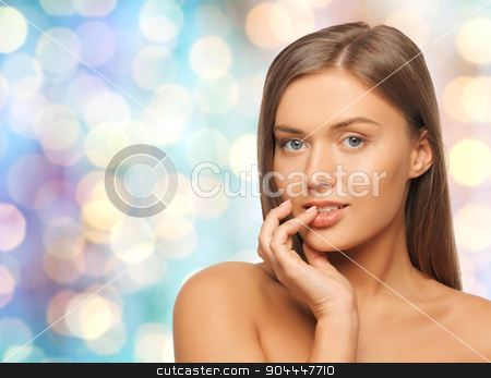 beautiful young woman with bare shoulders stock photo, beauty, people and health concept - beautiful young woman with bare shoulders over blue holidays lights background by Syda Productions
