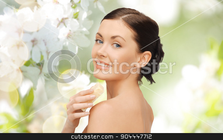 woman with soap bar over cherry blossom background stock photo, people, beauty, hygiene and summer concept - beautiful woman with soap bar over green cherry blossom background by Syda Productions