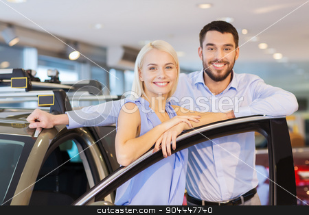 happy couple buying car in auto show or salon stock photo, auto business, car sale, consumerism and people concept - happy couple buying car in auto show or salon by Syda Productions