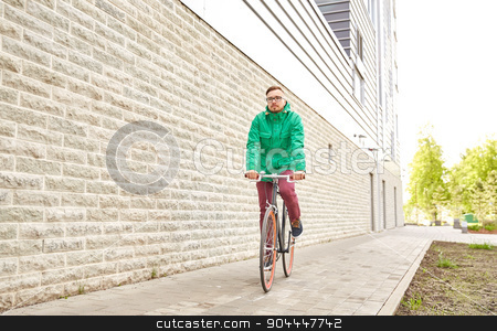 young hipster man riding fixed gear bike stock photo, people, style, leisure and lifestyle - young hipster man riding fixed gear bike on city street over building brick wall background by Syda Productions