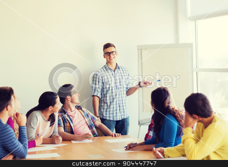 group of smiling students with white board stock photo, education, teamwork and people concept - smiling students with white board sitting an table indoors by Syda Productions