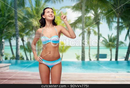 happy woman in bikini pointing finger up on beach stock photo, people, travel, swimwear and summer concept - happy young woman in bikini swimsuit pointing finger up to something imaginary over tropical beach with palm trees and pool at hotel resort background by Syda Productions