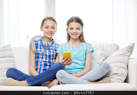 happy girls with smartphone sitting on sofa stock photo, people, children, technology, friends and friendship concept - happy little girls with smartphone sitting on sofa at home by Syda Productions
