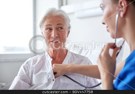 nurse with stethoscope and senior woman at clinic stock photo, medicine, age, support, health care and people concept - doctor or nurse with stethoscope visiting senior woman and checking her breath or heartbeat at hospital ward by Syda Productions