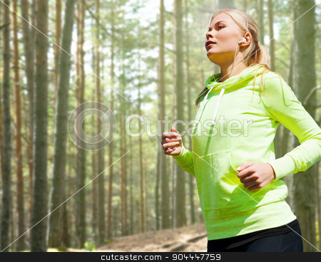 happy woman running or jogging stock photo, people, sport, fitness and slimming concept - happy woman running or jogging over woods background by Syda Productions
