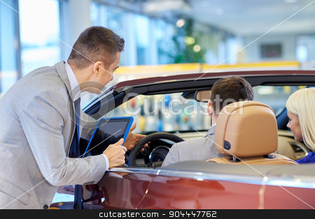 happy couple with car dealer in auto show or salon stock photo, auto business, car sale, consumerism and people concept - happy couple sitting in cabriolet with car dealer in auto show or salon by Syda Productions