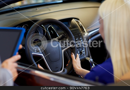 woman and car dealer with tablet pc in auto salon stock photo, auto business, car sale, technology and people concept - close up of woman and car dealer hands with tablet pc computer in auto show or salon by Syda Productions