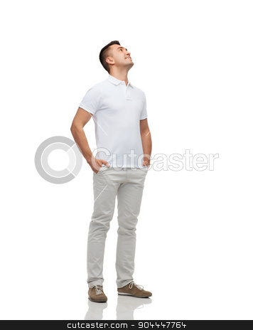smiling man with hands in pockets looking up stock photo, happiness and people concept - smiling man with hands in pockets looking up by Syda Productions