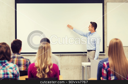 group of students and smiling teacher in classroom stock photo, education, high school, teamwork and people concept - smiling teacher standing in front of students and showing something on white board in classroom by Syda Productions