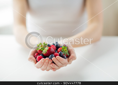 close up of woman hands holding berries stock photo, healthy eating, dieting, vegetarian food and people concept - close up of woman hands holding berries at home by Syda Productions