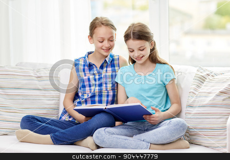 two happy girls reading book at home stock photo, people, children, friends, literature and friendship concept - two happy girls sitting on sofa and reading book at home by Syda Productions