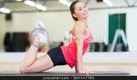 beautiful sporty woman doing exercise at gym stock photo, fitness, sport, training, gym and lifestyle concept - beautiful sporty woman doing exercise on the floor at gym by Syda Productions