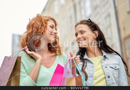 happy young women with shopping bags in city stock photo, vacation, sale, leisure, consumerism and friendship concept - smiling happy young women or teenage girls with shopping bags on city street by Syda Productions