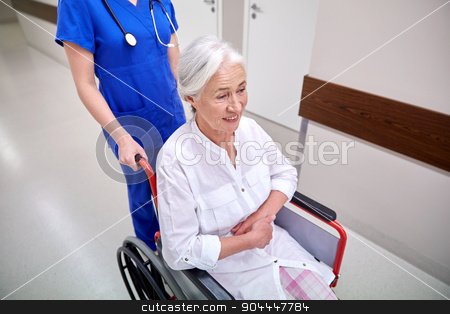 nurse with senior woman in wheelchair at hospital stock photo, medicine, age, support, health care and people concept - nurse taking senior woman patient in wheelchair at hospital corridor by Syda Productions