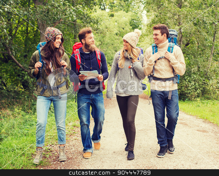 group of smiling friends with backpacks hiking stock photo, adventure, travel, tourism, hike and people concept - group of smiling friends with backpacks and map walking outdoors by Syda Productions