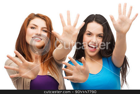 two smiling girls showing their palms stock photo, happiness and people concept - two smiling girls showing their palms by Syda Productions
