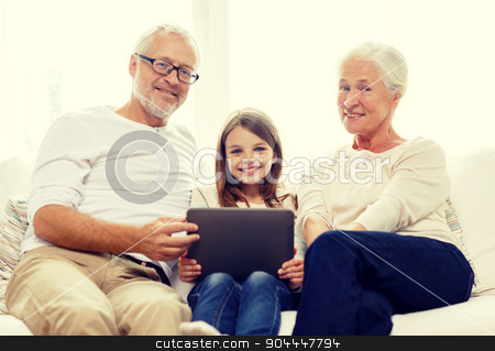smiling family with tablet pc at home stock photo, family, generation, technology and people concept - smiling grandfather, granddaughter and grandmother with tablet pc computer sitting on couch at home by Syda Productions
