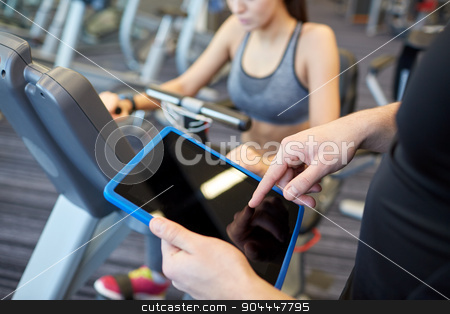 close up of trainer hands with tablet pc in gym stock photo, sport, fitness, lifestyle, technology and people concept - close up of trainer hands with tablet pc computer and woman working out on exercise bike in gym by Syda Productions