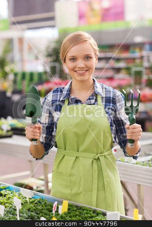 happy woman with gardening tools in greenhouse stock photo, people, gardening tools and profession concept - happy woman or gardener with trowel and fork in greenhouse by Syda Productions