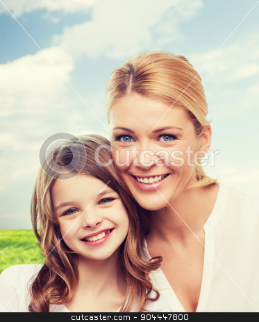 smiling mother and little girl stock photo, family, childhood, happiness and people - smiling mother and little girl over blue sky and grass background by Syda Productions
