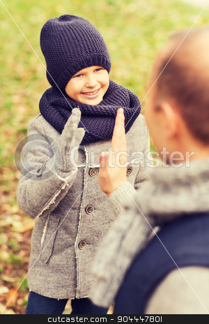 happy father and son making high five in park stock photo, family, childhood, season, gesture and people concept - happy father and son making high five in autumn park by Syda Productions