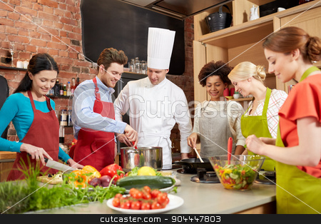 happy friends and chef cook cooking in kitchen stock photo, cooking class, culinary, food and people concept - happy group of friends and male chef cook cooking in kitchen by Syda Productions