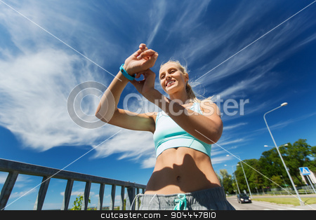 happy woman with heart rate watch and earphones stock photo, fitness, sport, people, technology and healthy lifestyle concept - smiling young woman with heart rate watch and earphones exercising outdoors by Syda Productions
