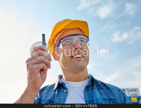 close up of builder in hardhat with walkie talkie stock photo, industry, building, technology and people concept - close up of male builder in hardhat with walkie talkie or radio outdoors by Syda Productions