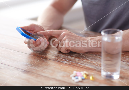 close up of hands with smartphone, pills and water stock photo, medicine, technology, nutritional supplements and people concept - close up of male hands smartphone, pills and water on table by Syda Productions