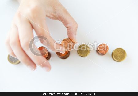 close up of female hand putting coins into columns stock photo, business and money saving concept - close up of female hand putting euro coins into columns in office by Syda Productions