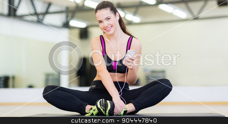 smiling girl with smartphone and earphones in gym stock photo, fitness, sport, training, gym, technology and lifestyle concept - smiling teenage girl with smartphone and earphones in gym by Syda Productions