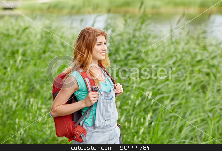 smiling young woman with backpack hiking in woods stock photo, adventure, travel, tourism, hike and people concept - smiling young woman with backpack hiking in woods by Syda Productions
