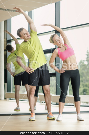 smiling man and woman exercising in gym stock photo, sport, fitness, lifestyle and people concept - smiling man and woman stretching in gym by Syda Productions