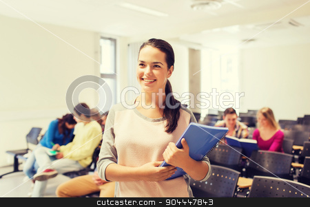 group of smiling students in lecture hall stock photo, education, high school, teamwork and people concept - group of smiling students with notepads sitting in lecture hall by Syda Productions