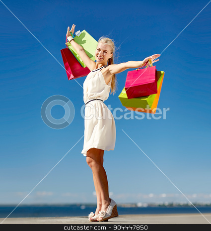 smiling woman with shopping bag rising hands stock photo, consumerism, sale and people concept - smiling woman with shopping bag rising hands by Syda Productions