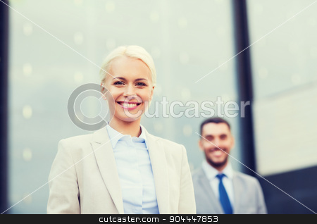close up of smiling businessmen stock photo, business, partnership, success and people concept - close up of smiling businessman and businesswoman standing over office building by Syda Productions