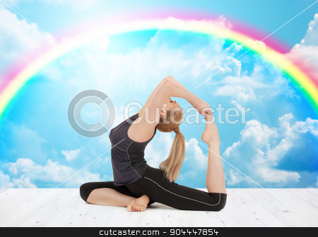 happy young woman doing yoga exercise stock photo, sport, fitness, yoga, people and health concept - happy young woman doing headstand exercise on wooden berth over white clouds and rainbow on blue sky background by Syda Productions
