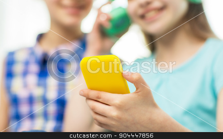 close up of girls with smartphone and headphones stock photo, people, children, technology and friends concept - close up of happy little girls with smartphone and earphones listening to music by Syda Productions