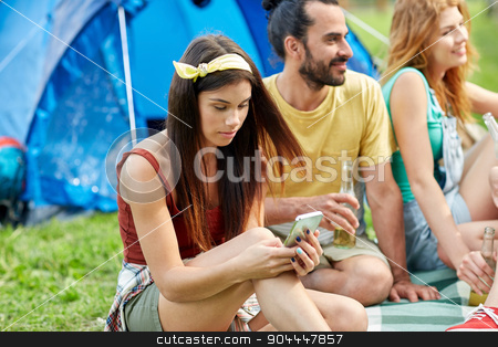 happy woman with smartphone and friends at camping stock photo, travel, tourism, hike, technology and people concept - happy young woman with smartphone and friends at camping by Syda Productions