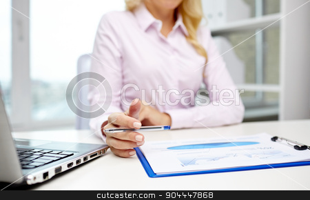 smiling businesswoman reading papers in office stock photo, education, business, people and technology concept - close up of smiling businesswoman with laptop computer and papers sitting in office by Syda Productions