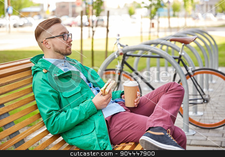 happy young hipster man with coffee and sandwich stock photo, people, style, leisure and lifestyle - happy young hipster man with coffee cup and sandwich eating and drinking on city street by Syda Productions