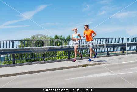 smiling couple running at summer seaside stock photo, fitness, sport, friendship and healthy lifestyle concept - smiling couple running at summer seaside by Syda Productions