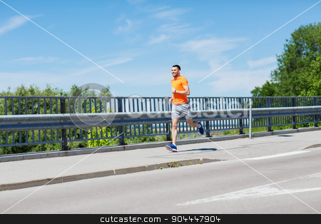 smiling young man running at summer seaside stock photo, fitness, sport, people, technology and healthy lifestyle concept - smiling young man with heart rate watch running at summer seaside by Syda Productions