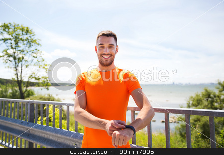 smiling young man with smart wristwatch at seaside stock photo, fitness, sport, people, technology and healthy lifestyle concept - smiling young man with smart wristwatch at summer seaside by Syda Productions
