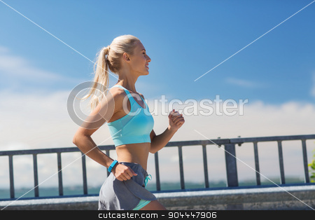 smiling young woman running outdoors stock photo, fitness, sport, people and healthy lifestyle concept - smiling young woman with heart rate watch running outdoors by Syda Productions