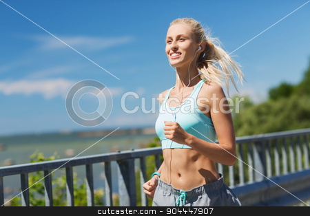 smiling young woman running outdoors stock photo, fitness, sport, people, music and healthy lifestyle concept - smiling young woman with earphones running outdoors by Syda Productions