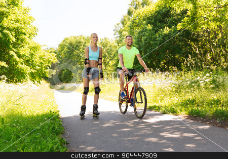 happy couple with rollerblades and bicycle riding stock photo, fitness, sport, summer, people and healthy lifestyle concept - happy couple with rollerblades and bicycle riding outdoors at summer by Syda Productions